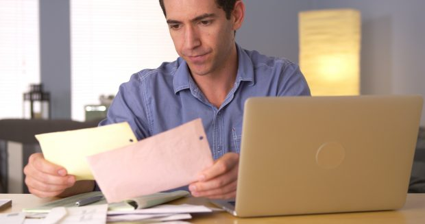 Image of a Man worries while looking through his bills - Represents schoolteacher concerned with bills before making million dollars