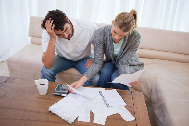 Image of a couple worried going through their bills - Represents that you should learn the truth about budget and never worry about being able to pay your bills anymore