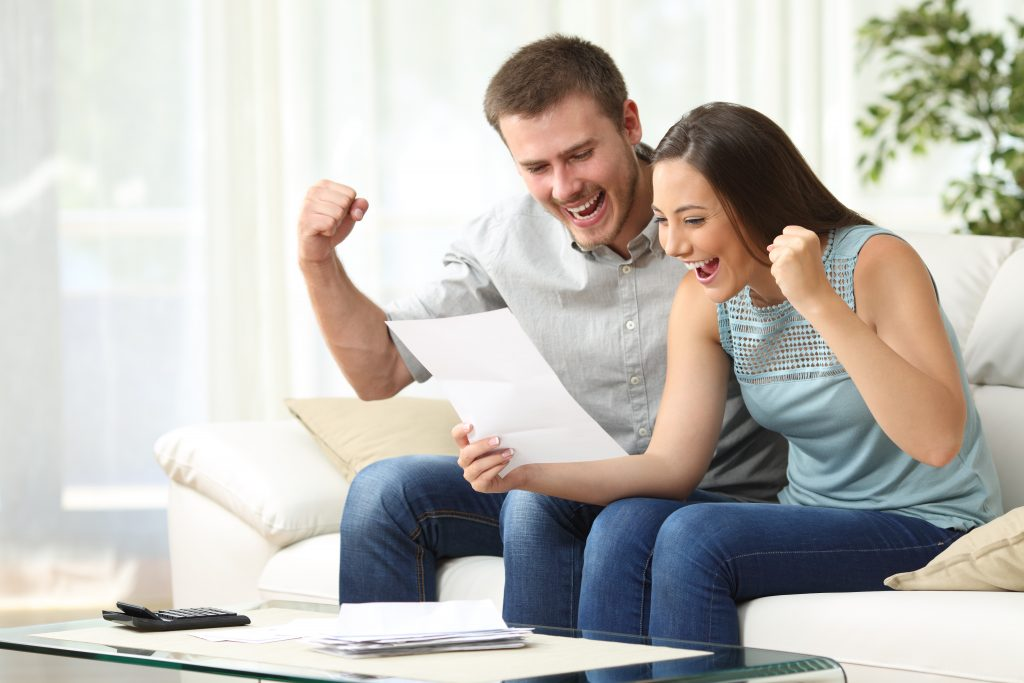 Image of a couple celebrating at home - represents that you should learn the truth about budget and start enjoying life as it should be