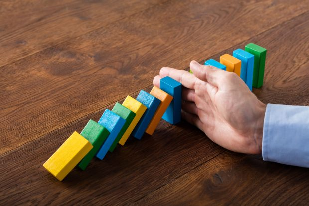 Image of a hand stopping a line of domino pieces form falling - represents that you should learn the truth about budgets and stop doing things that don't work